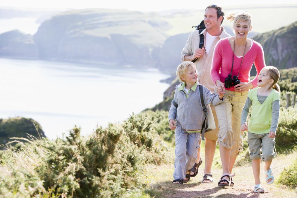 Family walking on cliffside path